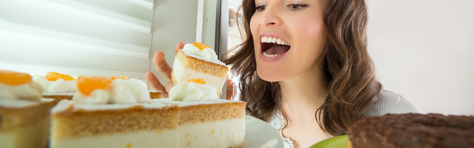 Hungry Young Woman Eating Slice Of Cake From Fridge At Home