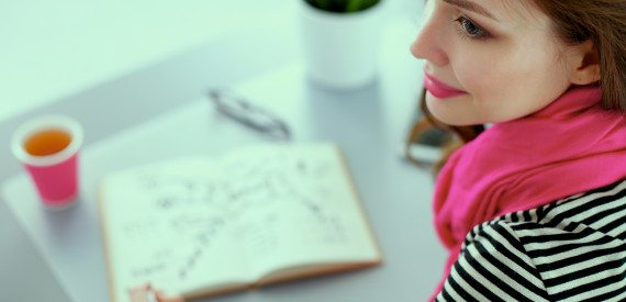 Young woman writes to diary on a white table .